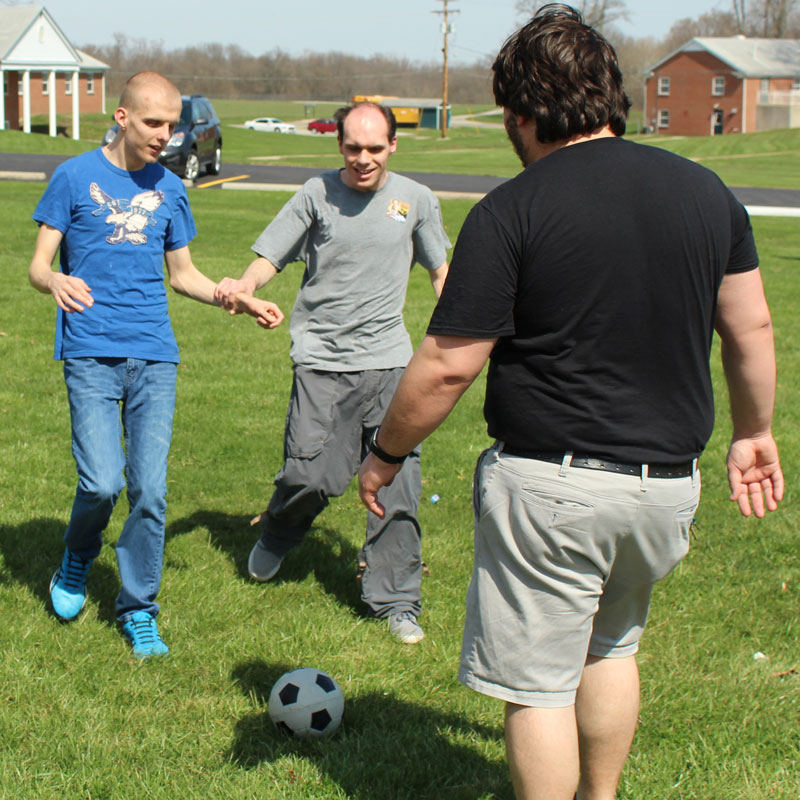 Residents playing soccer with volunteer