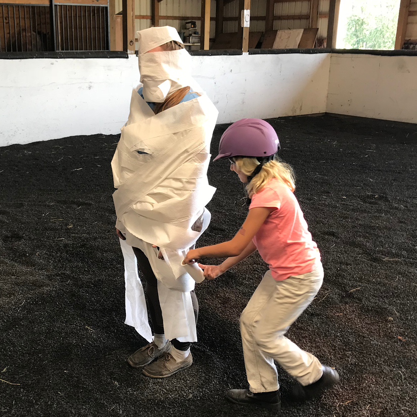 Equestrian Center at Beverly Farm Summer Riding Camps. Girl has fun TPing an instructor using a roll of toilet paper during one of the camps memorable fun activity times.