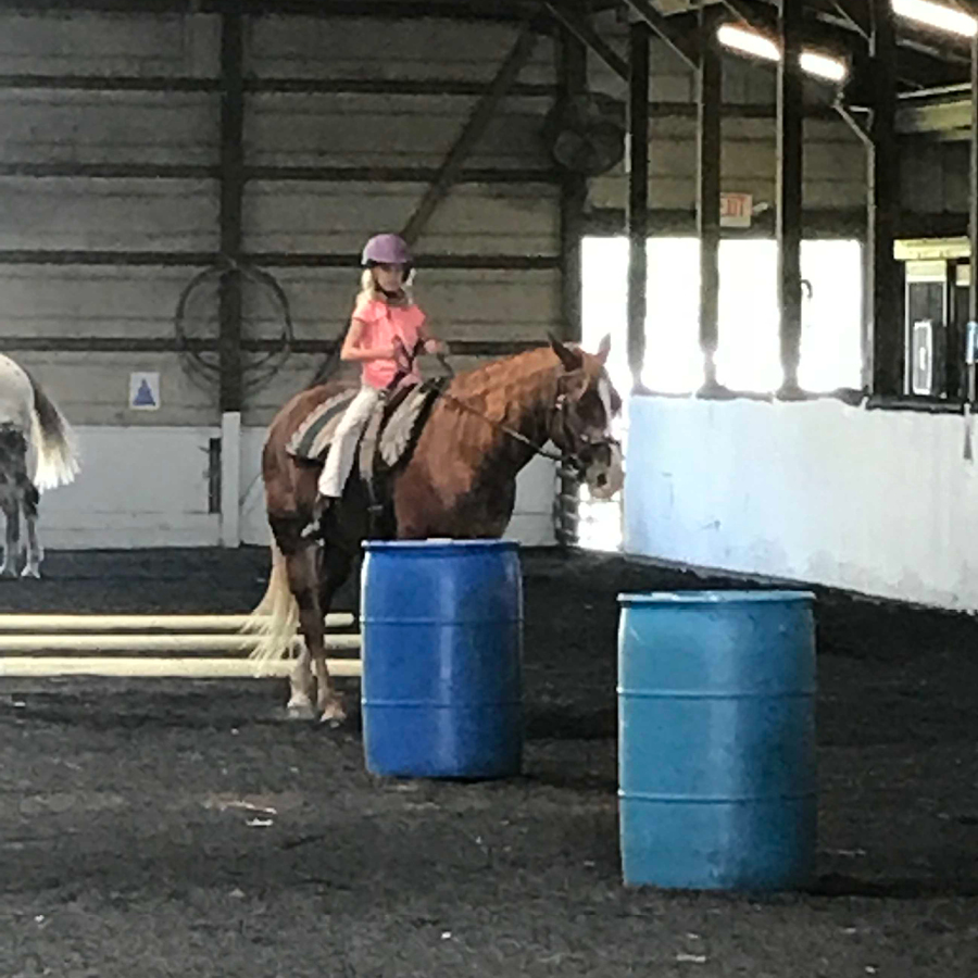 Equestrian Center at Beverly Farm Summer Riding Camps. Girl on horseback in our indoor arena about to go through the barrel course.