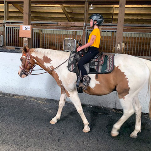 Equestrian Center at Beverly Farm Riding Lessons. Girl on horseback riding in the indoor arena.