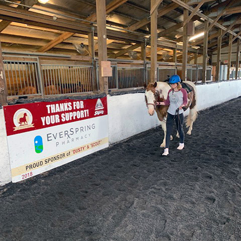Equestrian Center at Beverly Farm Riding Lessons. Woman leads her horse around the perimeter of the indoor arena.